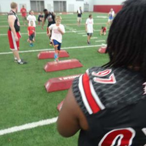 Louisville football players coaching kids