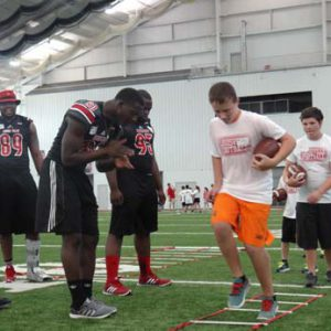 UofL players helping coach at the Just for Kids Football Clinic