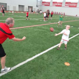 Bobby Petrino passing a football at the Just for Kids Football Clinic