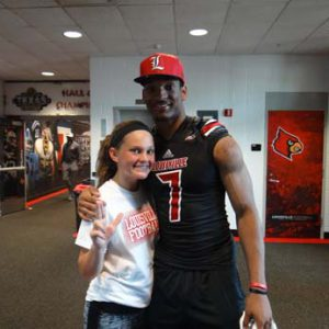 a UofL football player with a fan